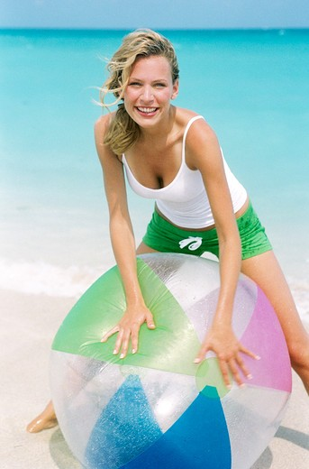 Stock Photo: 4288-1121 Young woman playing on beach with striped beach ball.