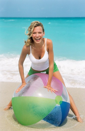 Stock Photo: 4288-1122 Young woman playing on beach with striped beach ball.