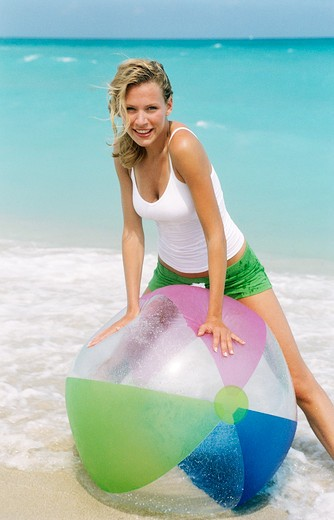 Stock Photo: 4288-1123 Young woman playing on beach with striped beach ball.