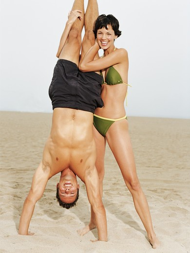 Young woman in bikini holding man in handstand on sandy beach. : Stock Photo