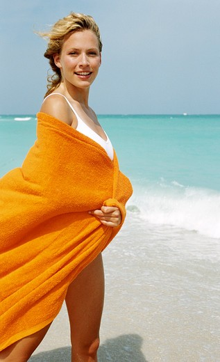 Young blonde wrapped in orange towel on beach. : Stock Photo