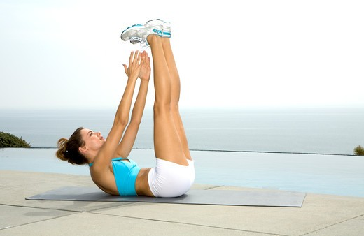 Stock Photo: 4288-1128 Tan brunette exercising outdoors in blue and white workout clothing.