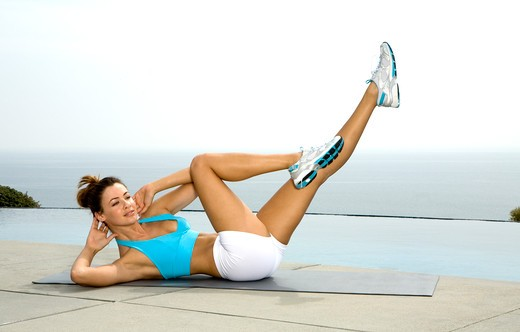 Tan brunette exercising outdoors in blue and white workout clothing. : Stock Photo