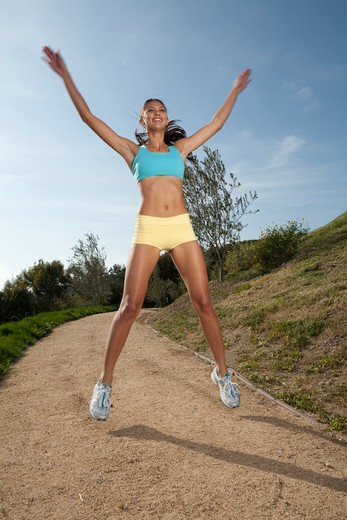 Stock Photo: 4288-1134 Young woman doing jumping jacks outdoors in shorts and sports bra.