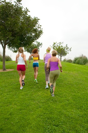 Stock Photo: 4288-1140 Four women running on grass.