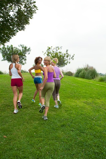 Four women running on grass. : Stock Photo