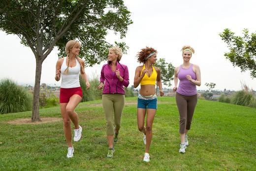 Stock Photo: 4288-1142 Four women running on grass.