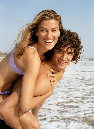 Stock Photo: 4288-1146 Young man giving woman piggyback ride on beach.
