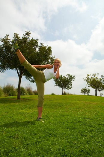 Stock Photo: 4288-1147 Blonde woman practicing high kick in park.