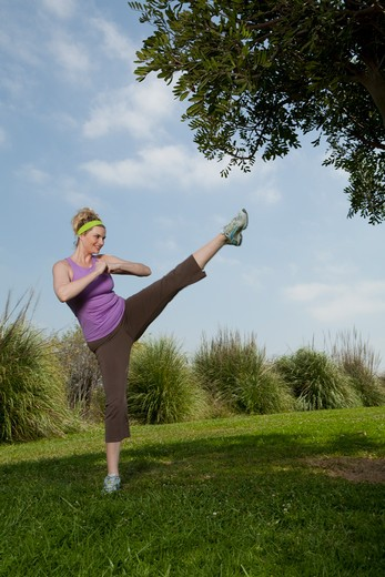Blonde woman practicing high kick in park. : Stock Photo