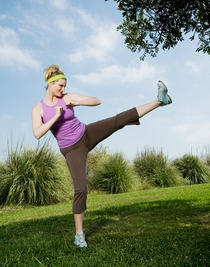 Stock Photo: 4288-1150 Blonde woman practicing high kick in park.