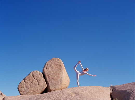 Stock Photo: 4288-1158 Young woman in silver bodysuit in yoga pose among rocks.