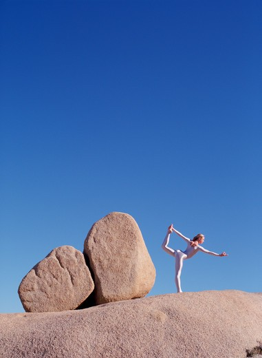 Young woman in silver bodysuit in yoga pose among rocks. : Stock Photo