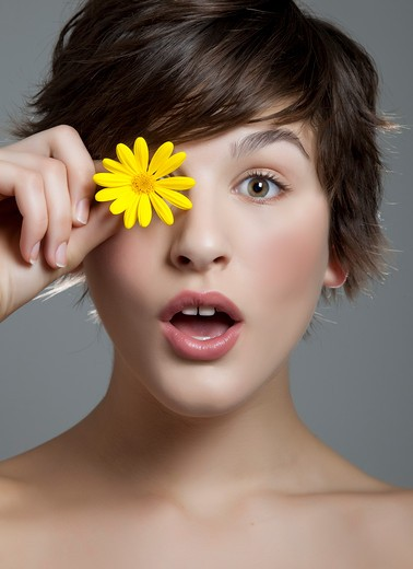 Short-haired brunette with yellow daisy. : Stock Photo