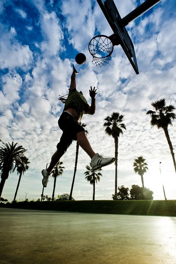 Man with dreadlocks making a jump shot on outdoor basketball court. : Stock Photo