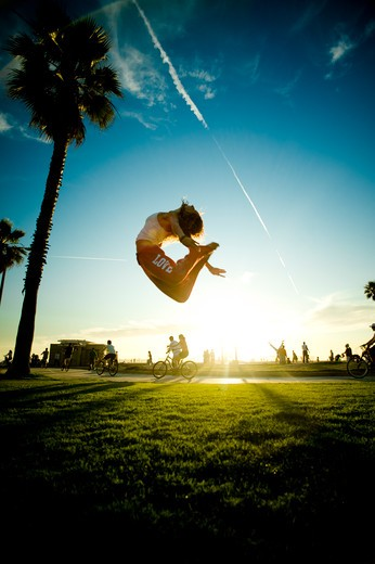 Woman in white tank top and red pants jumping in park with palm trees. : Stock Photo