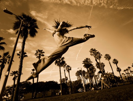 Stock Photo: 4288-1231 Young woman wearing bikini and pants leaping in park with palm trees.