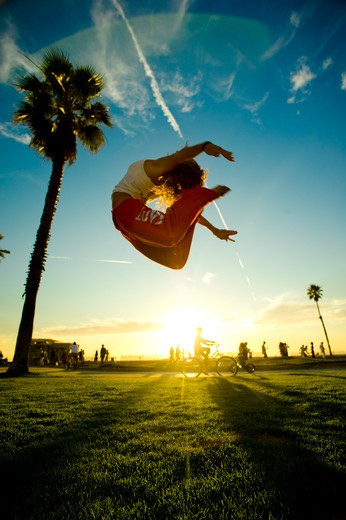 Stock Photo: 4288-1233 Woman in white tank top and red pants jumping in park with palm trees.