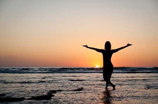 Stock Photo: 4288-1245 Woman dancing in water at sunset.