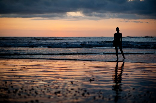 Backlit woman standing on beach at sunset. : Stock Photo
