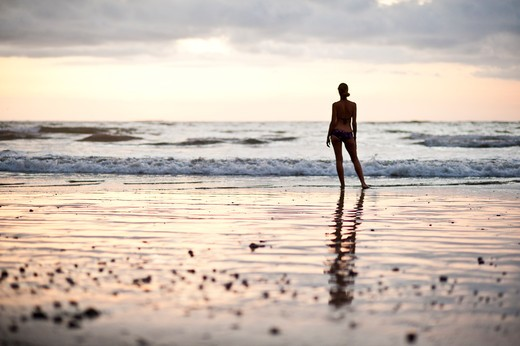 Stock Photo: 4288-1253 Backlit woman standing on beach at sunset.