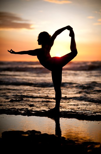 Backlit woman stretching on beach at dawn. : Stock Photo