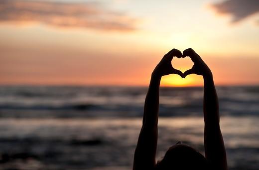 Backlit hands make heart shape at sunset. : Stock Photo