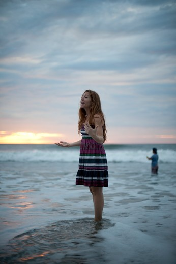 Girl in striped dress on beach at dawn. : Stock Photo