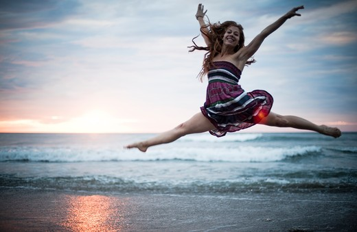 Stock Photo: 4288-1276 Woman in striped dress dancing on beach at dawn.