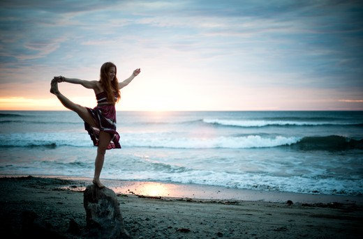 Woman in striped dress dancing on beach at dawn. : Stock Photo