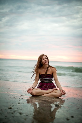 Woman in striped dress sitting on beach at dawn. : Stock Photo