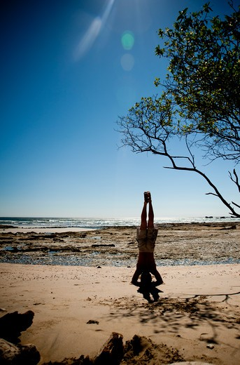 Stock Photo: 4288-1299 Man doing headstand on beach.