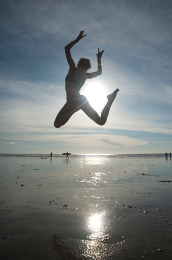 Stock Photo: 4288-1303 Woman dances on beach in morning light.