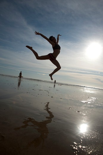 Stock Photo: 4288-1304 Woman dances on beach in morning light.