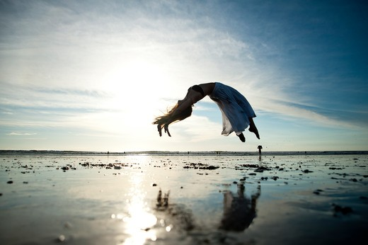 Woman dances on beach in morning light. : Stock Photo