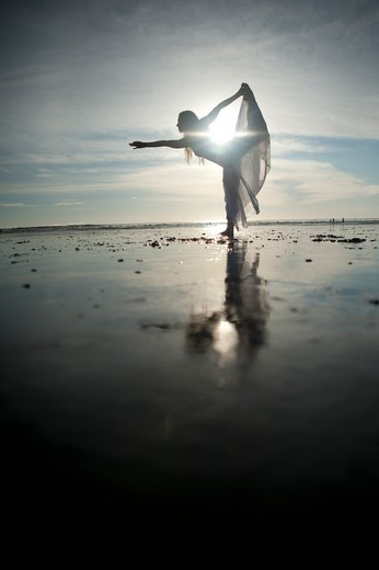 Stock Photo: 4288-1314 Woman stretches on beach in morning light.