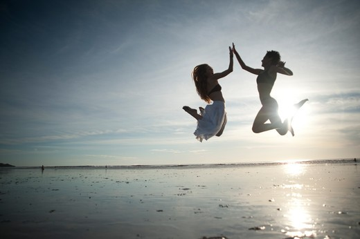 Stock Photo: 4288-1315 Two women mid-air high five on beach.
