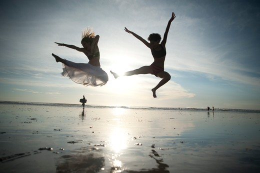 Stock Photo: 4288-1316 Two backlit women jump on beach.