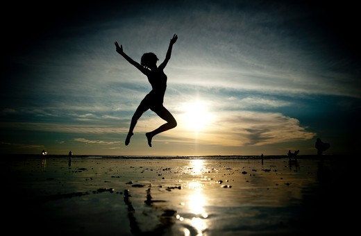 Backlit woman dances on beach in morning light. : Stock Photo