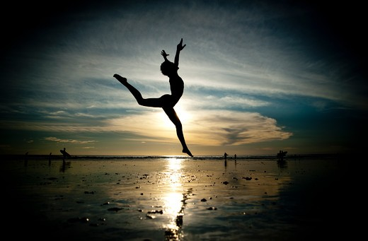 Stock Photo: 4288-1328 Backlit woman dances on beach in morning light.