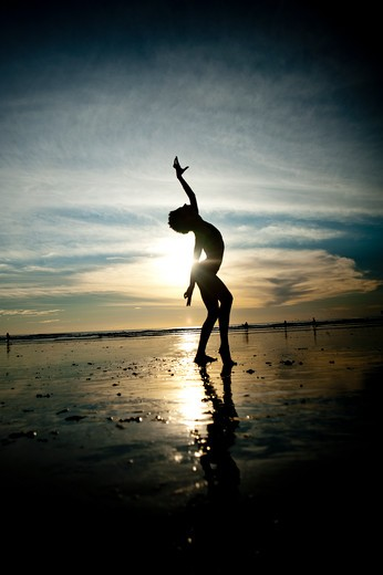 Stock Photo: 4288-1329 Backlit woman dances on beach in morning light.