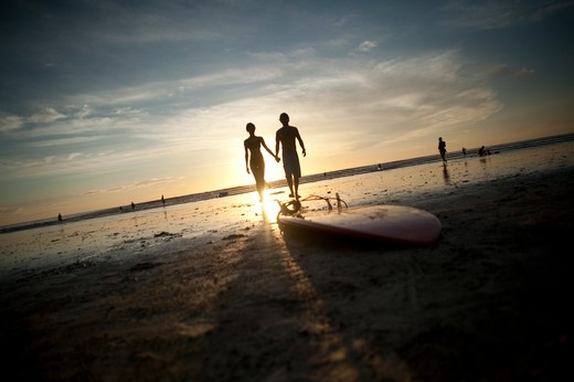 Backlit people walking toward surfboard on beach. : Stock Photo