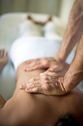 Masseuse massages back. : Stock Photo