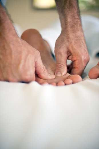 Stock Photo: 4288-1347 Masseuse massages foot.