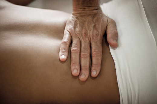 Stock Photo: 4288-1349 Masseuse massages lower back.