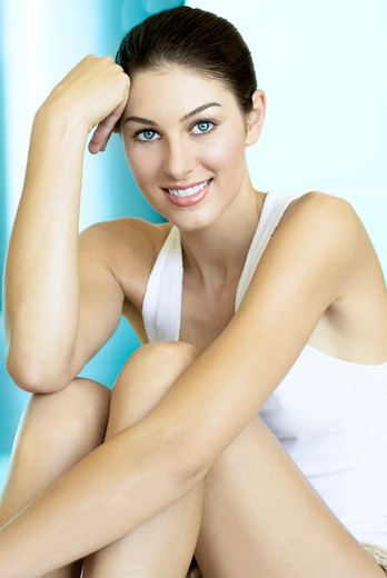 Seated brunette in a white tank top in front of aqua backdrop. : Stock Photo