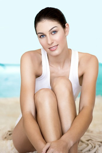 Stock Photo: 4288-1361 Seated brunette in a white tank top with beach backdrop.