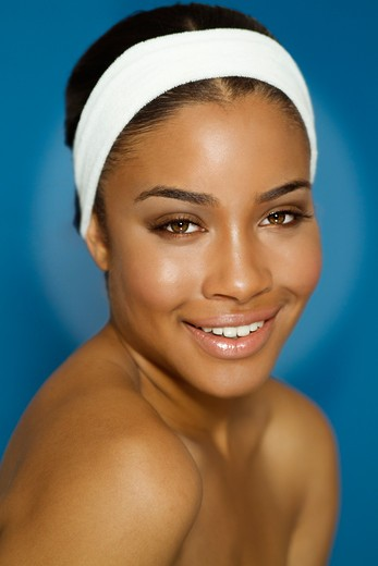 Stock Photo: 4288-1380 Young African-American woman with bare shoulders and white terrycloth headband.