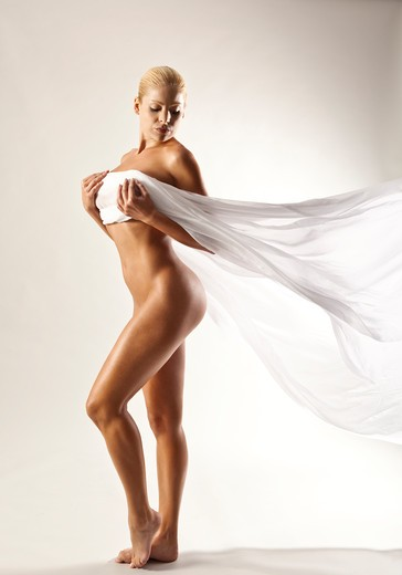 Stock Photo: 4288-1410 Side view of nude blonde Caucasian woman with billowing white cloth on a white background.
