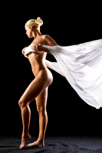Stock Photo: 4288-1416 Side view of nude blonde Caucasian woman with billowing white cloth on a black background.